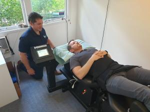 Man on spinal decompression bed receiving treatment from physiotherapist