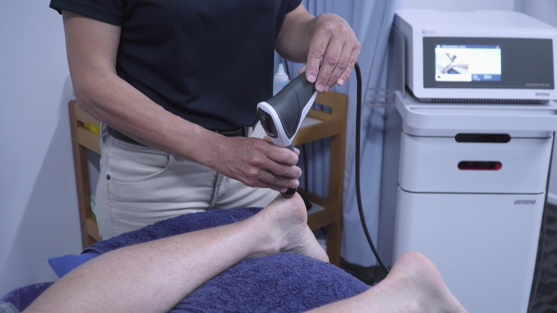 A physiotherapist providing shockwave therapy treatment to the heel of a patient who is laying on a treatment bed